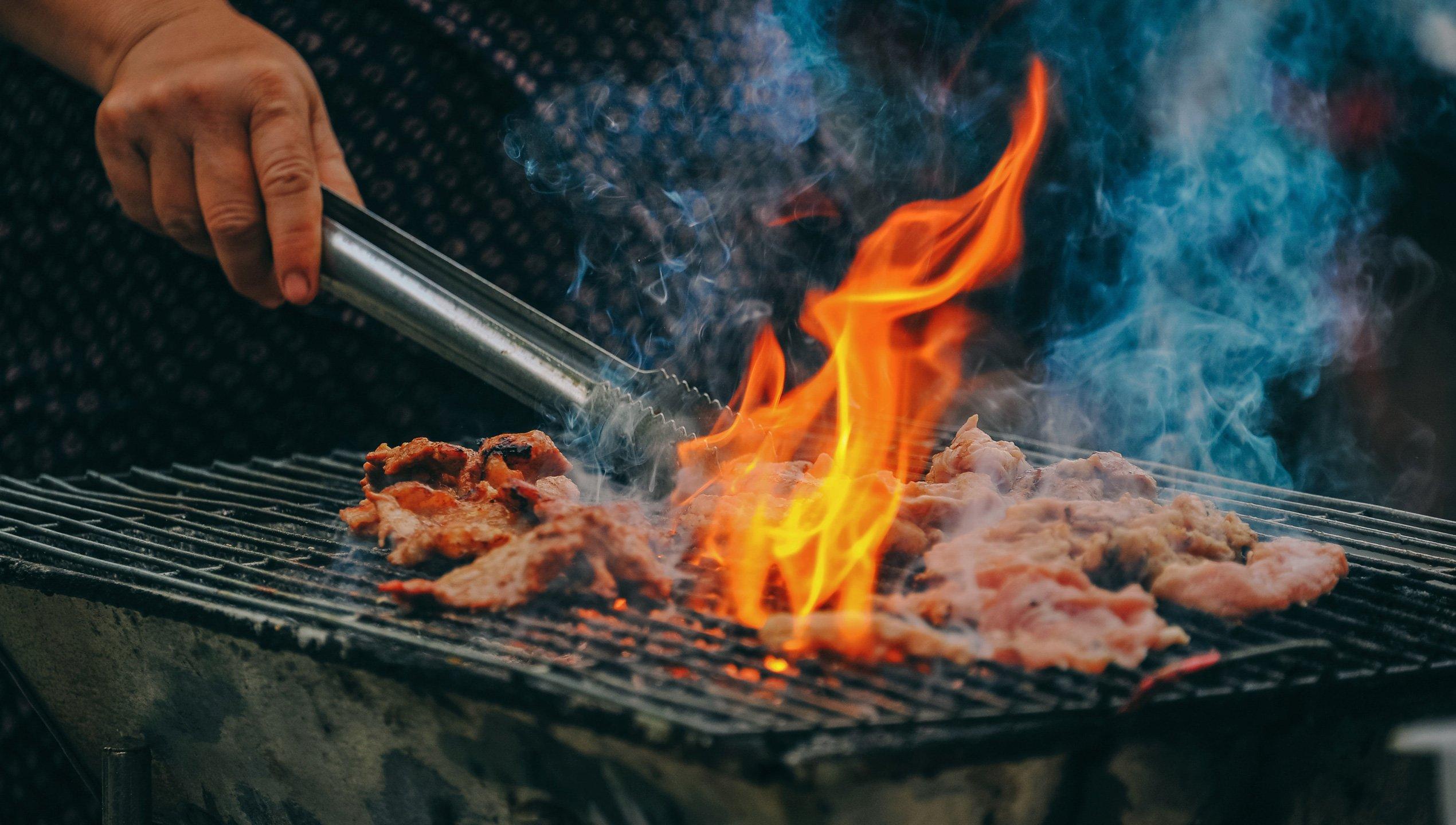 Abbildung zur Privathaftpflichtversicherung - Holzkohlegrill mit Grillfleisch